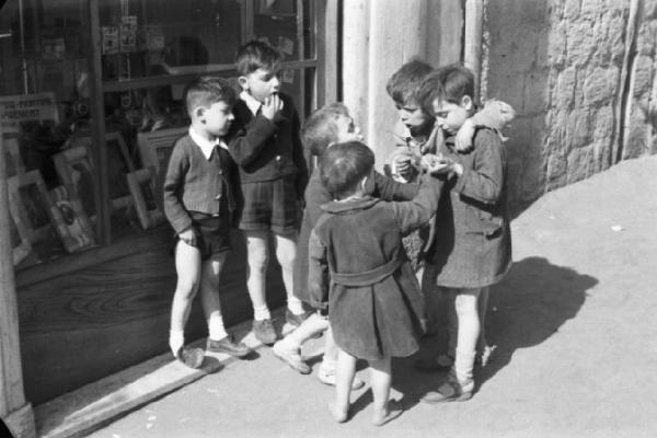 Napoli, 1946. Bambini giocano lungo la strada in prossimità del negozio di un fotografo. Fonte: LombardiaBeniCulturali.